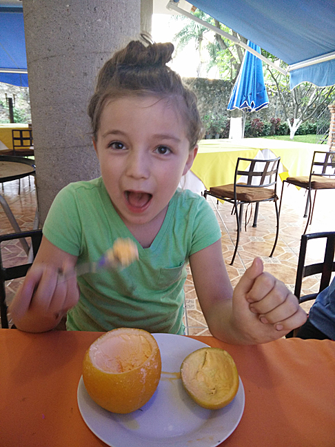 """Orange ice cream served in an orange """"bowl"""" with orange """"lid"""". Others at the table had pineapple, mamey, and apple, all in their own fruit containers. (At El Itacate)"""